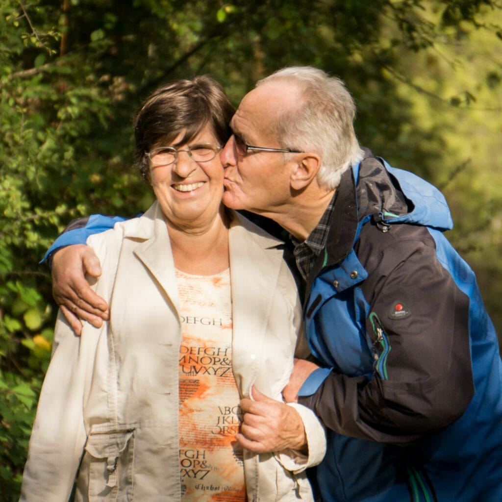 old man in retirement kissing his wife on the cheek in the park